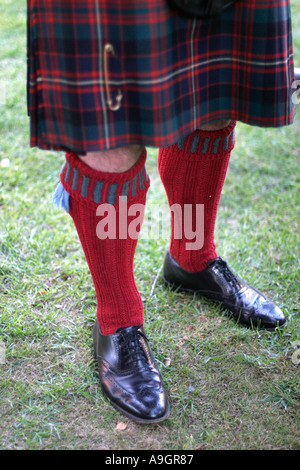 A Scottish kilt and hand knit red socks with gaiters - Stock Photo