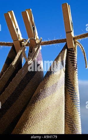 Three linen tea towels pegged on the washing line Tea towels woven by Alison Morton - Stock Photo