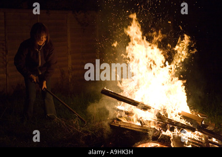 Woman tending to a bonfire - Stock Photo