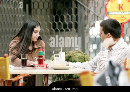 Young woman and man having lunch dinner outdoors with a friend eating salad drinking cola long black hair brunette - Stock Photo