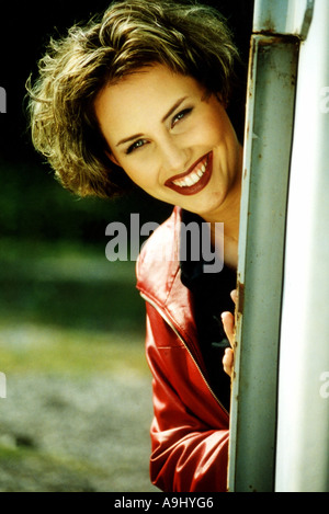 smiling woman looking around the edge of a house - Stock Photo