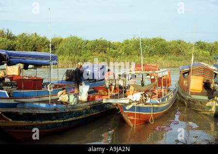 Fishermen unloading fishing boats, early morning, Chong Kneas floating village, Tonle Sap Lake, Siem Reap, Cambodia - Stock Photo