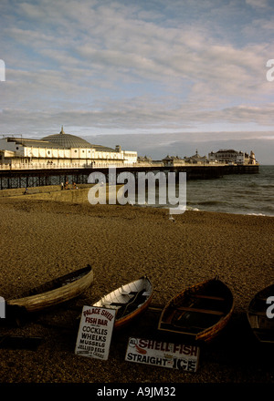 Victorian amusement pier on the seaside Brighton small wooden rownung boats pulled up on the shingle beach Shell - Stock Photo
