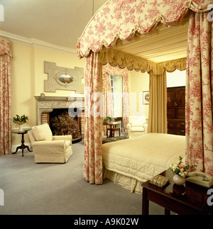 Pink and white toile-de-Jouy drapes on four-poster bed with tailored cream linen in cream bedroom - Stock Photo