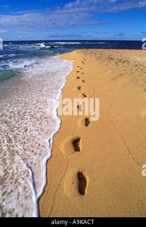 Evening light on footprints in sand along the surf at Tunnels Beach North Shore Island of Kauai Hawaii - Stock Photo