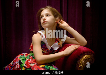 young girl posing on red couch in studio - Stock Photo