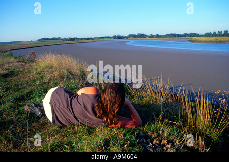 Woman lying down Butley Creek Suffolk England - Stock Photo