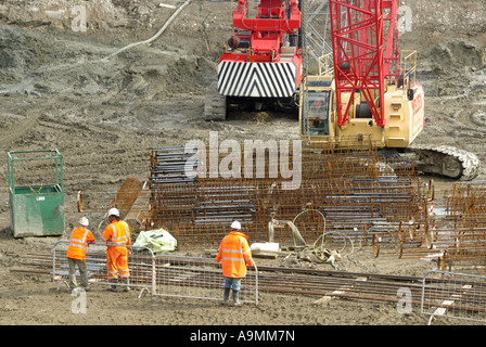 High vis building construction site worker assemble steel reinforcing cages for crane placing in pile bores for - Stock Photo