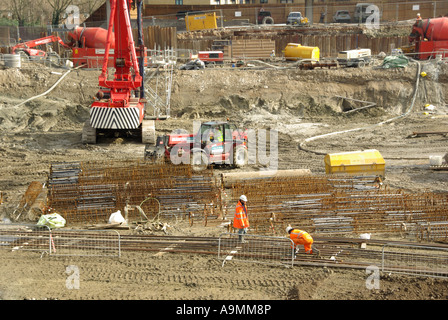 Construction site workmen assemble steel reinforcing cages ready for dropping into pile bores for concreting - Stock Photo