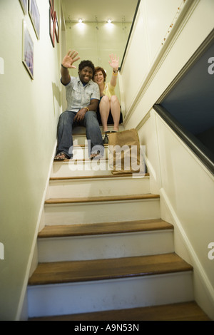Low angle view of a young inter-racial couple sitting on top of a stairway waving - Stock Photo