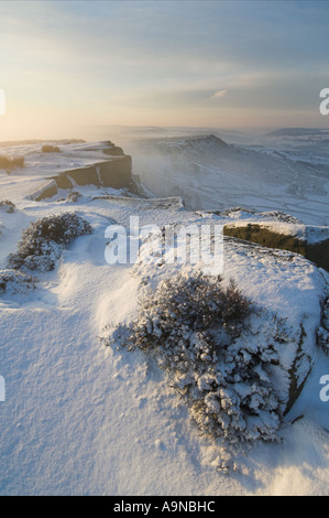 Sunrise on a misty winter morning with snow on Froggatt edge derbyshire peak district national park England UK GB - Stock Photo