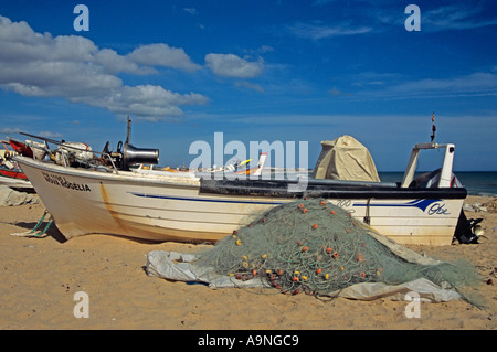 ARMACAO DE PERA ALGARVE PORTUGAL EUROPE Colourful red yellow white green fishing boats on golden sand Praia de Pescadores - Stock Photo