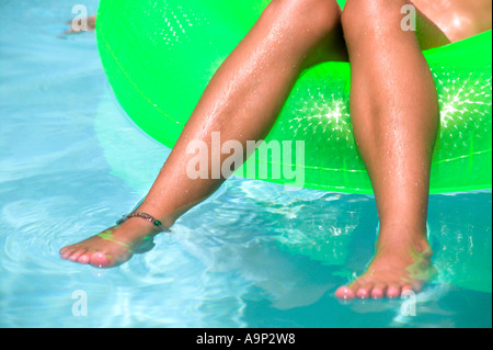 Young girl dangling her legs in pool Stock Photo