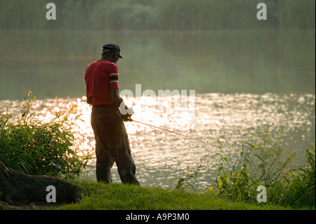 Man fishing in Juneau Lagoon at twilight Milwaukee Wisconsin USA - Stock Photo