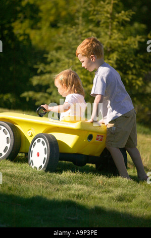 Brother pushing little sister in toy car - Stock Photo