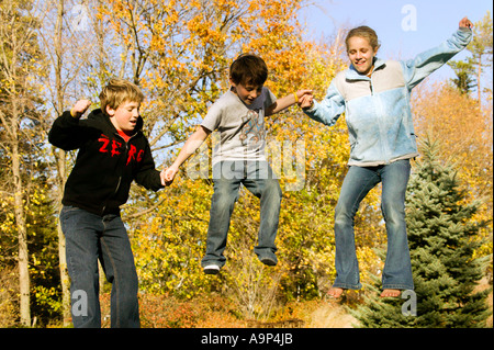Three jumping kids in midair with fall foliage - Stock Photo