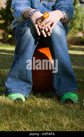 Hands and legs of girl sitting outside - Stock Photo