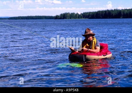 Fly Fisherman in a Belly Boat fishing for Trout in Hi Hium Lake in the Cariboo Region of British Columbia Canada - Stock Photo