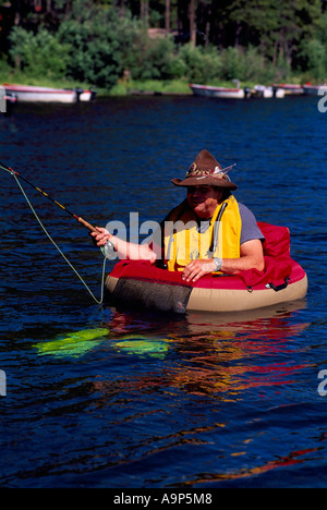 Fly Fisherman fishing for Trout while floating in a Belly Boat on Hi Hium Lake, Cariboo Region, BC, British Columbia, - Stock Photo