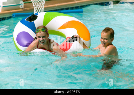 Brother and sister playing in pool - Stock Photo