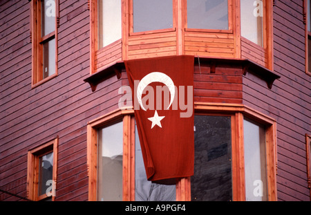 The Turkish national flag hangs on the facade of a typical clapboard house in Sultanahmet area Istanbul Turkey - Stock Photo