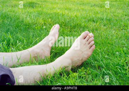 Vacation, Young Man's 'Bare Feet' 'Lying Down' in Fresh Grass Outdoors Relaxing Park Laziness relaxation - Stock Photo
