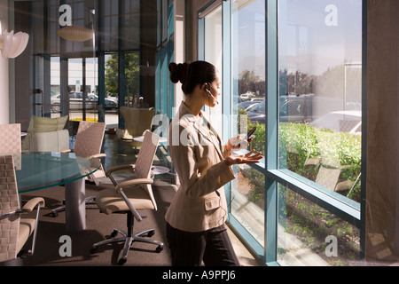 Businesswoman on cell phone in meeting room - Stock Photo