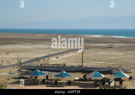 Israel Dead Sea Ein Gedi Spa view of few umbrellas in frgd with empty mud field and the receding ses in bkgd - Stock Photo