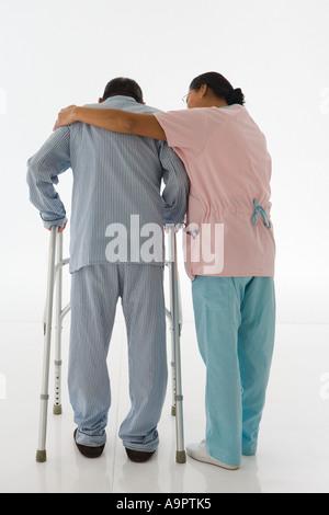 Nurse helping patient to walk - Stock Photo