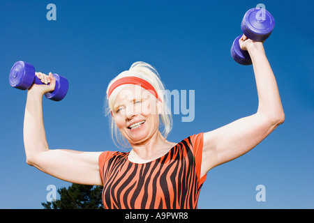 Senior adult woman lifting dumbbells - Stock Photo