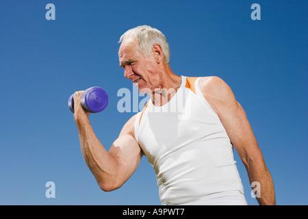 Senior adult man lifting a dumbbell - Stock Photo