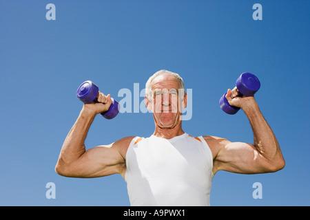 Senior adult man lifting dumbells - Stock Photo