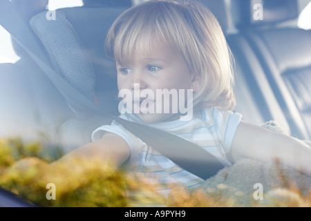 Young girl looking out of car window - Stock Photo