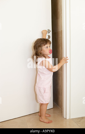 Young girl opening door - Stock Photo