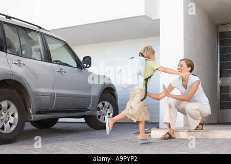 Boy returning home to his mother - Stock Photo
