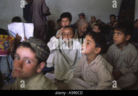 Young Afghan refugee children receiving a few hours basic education from an NGO funded project in Quetta Balochistan - Stock Photo