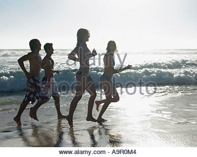 Friends running by the sea - Stock Photo
