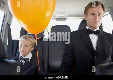 Man and boy in a car wearing dinner jackets - Stock Photo
