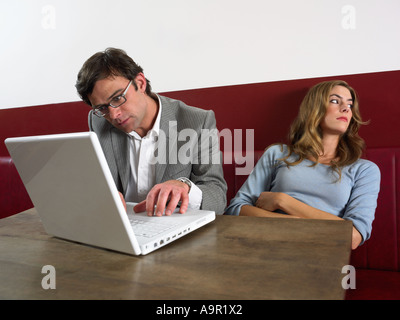 Woman bored as man works on computer - Stock Photo