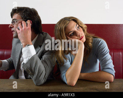 Woman bored as man talks on phone - Stock Photo