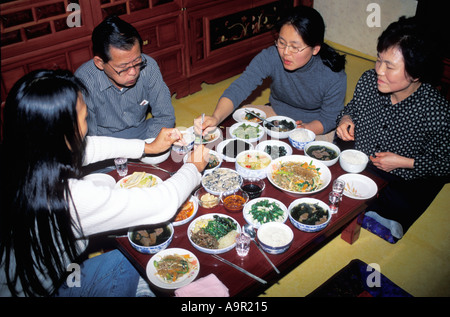Korean family eating traditional food in typical home setting - Stock Photo