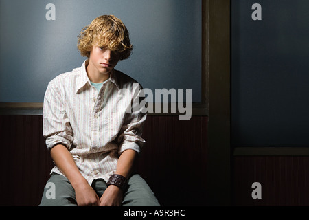 Teenage boy sat alone - Stock Photo