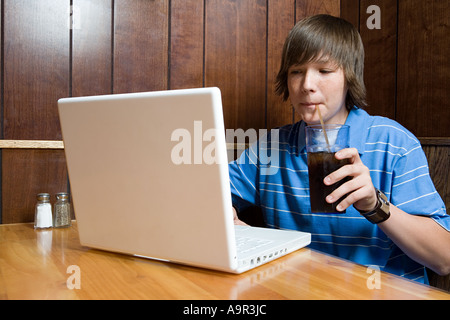 Teenage boy working on laptop in cafe - Stock Photo