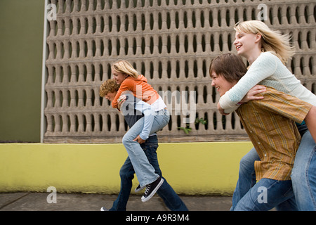 Four teenagers running piggy back races - Stock Photo
