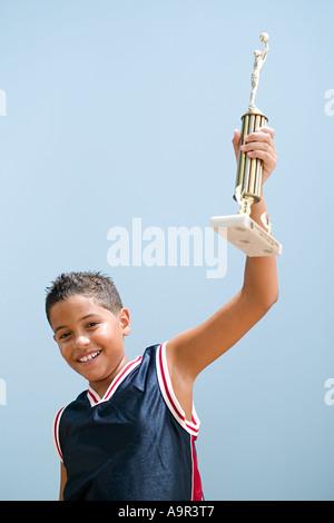 Boy holding up basketball trophy - Stock Photo