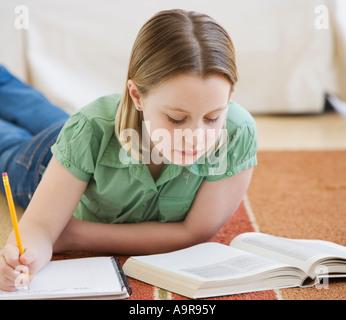 Girl doing homework on floor - Stock Photo
