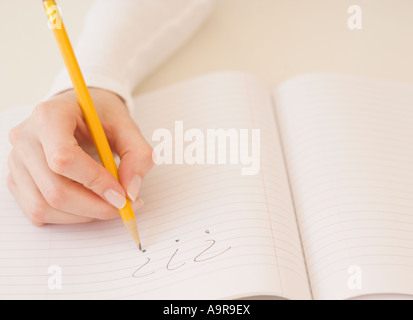 Woman writing question marks in notebook - Stock Photo
