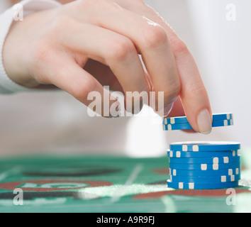 Woman picking up poker chips - Stock Photo