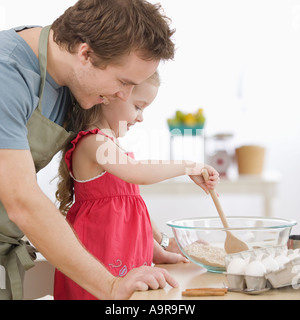 Father and daughter mixing batter in kitchen - Stock Photo