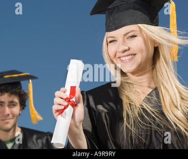Woman wearing graduation cap and gown with diploma - Stock Photo
